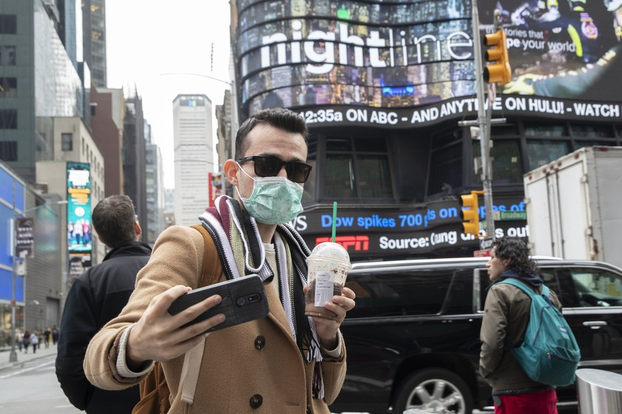 Justin Dalipi, of Albania, wears a mask as a precaution against the Corona virus during the final days of his visit to New York, as he takes a selfie in New York's Times Square, Tuesday, March 10, 2020. For most people, the new coronavirus causes only mild or moderate symptoms, such as fever and cough. For some, especially older adults and people with existing health problems, it can cause more severe illness, including pneumonia. The vast majority of people recover from the new virus. (AP Photo/Mary Altaffer)