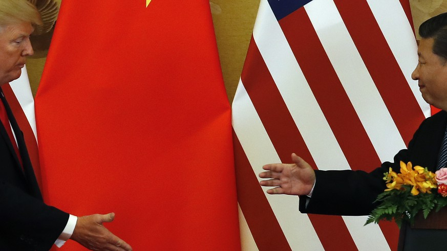 In this Nov. 9, 2017, photo, U.S. President Donald Trump, left, and Chinese President Xi Jinping prepare to shake their hands after a joint press conference at the Great Hall of the People in Beijing. The brewing China-U.S. trade conflict features two leaders who've expressed friendship but are equally determined to pursue their nation's interests and their own political agendas. But while Trump faces continuing churn in his administration and a tough challenge in midterm congressional elections, Xi leads an outwardly stable authoritarian regime. Xi recently succeeded in pushing through a constitutional reform allowing him to rule for as long as he wishes while facing no serious electoral challenge. (AP Photo/Andy Wong)