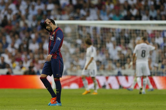 Barcelona's Gerard Pique rubs his brow during a Spanish La Liga soccer match between Real Madrid and Barcelona at the Santiago Bernabeu stadium in Madrid, Spain, Saturday Oct. 25, 2014. (AP Photo/Paul White)