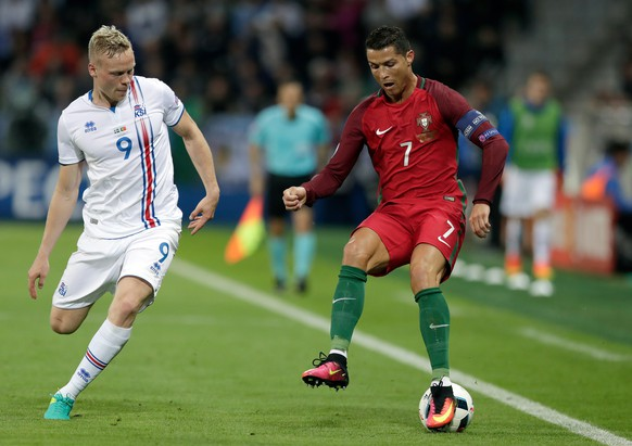 Portugal's Cristiano Ronaldo, right, drives the ball around Iceland's Kolbeinn Sigthorsson during the Euro 2016 Group F soccer match between Portugal and Iceland at the Geoffroy Guichard stadium in Saint-Etienne, France, Tuesday, June 14, 2016. (AP Photo/Pavel Golovkin)