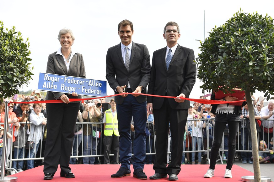 epa05270517 Swiss Tennis player Roger Federer (C) cuts the red ribbon next to Erich Fehr (R), Mayor of the city of Biel and Barbara Schwickert (L), local council of Biel, during the inauguration of the 'Roger-Federer-Allee'-alley in Biel-Bienne, Switzerland,  21 April 2016. Swiss Tennis association
