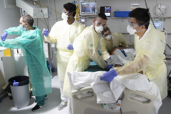 Medical workers, center and left, treat a patient with COVID-19 with the help of 3 soldiers of the Swiss army in the intensive care unit at the University Hospital (CHUV) during the state of emergency of the coronavirus disease (COVID-19) outbreak, in Lausanne, Switzerland, Friday, April 3, 2020. Countries around the world are taking increased measures to stem the widespread of the SARS-CoV-2 coronavirus which causes the Covid-19 disease. (KEYSTONE/POOL/Laurent Gillieron)