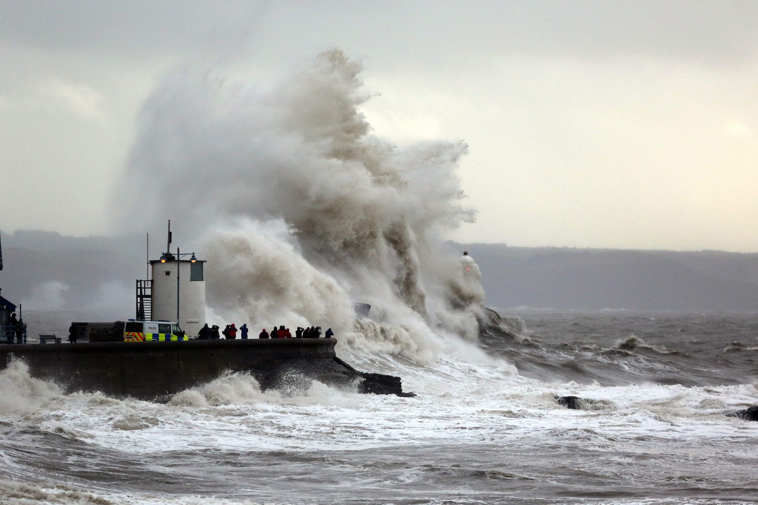 epa04055793 Wave-watchers gather on the quayside as storm-driven waves crash against the lighthouse wall in the coastal resort of Porthcawl, south Wales, United Kingdom 5 February 2014. Atlantic storms continue to battle the south west british coastline causing fresh  travel chaos, cutting power and causing more flooding  EPA/DMITRIS LEGAKIS