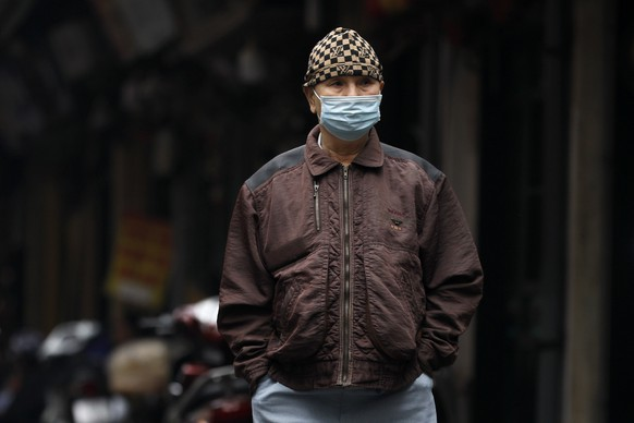 epa08924406 A man wearing a face mask walks at a street in Hanoi, Vietnam, 07 January 2021. Vietnam has agreed to buy some 30 million doses of the coronavirus disease (COVID-19) vaccine made by the British company AstraZeneca, according to information from Vietnam's Health Ministry.