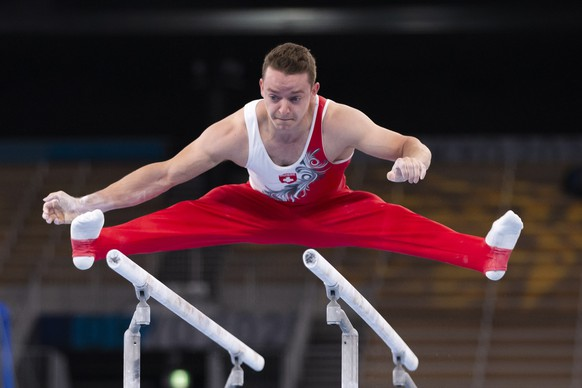 Christian Baumann of Switzerland performs on the parallel bars during the men's artistic gymnastics qualification at the 2020 Tokyo Summer Olympics in Tokyo, Japan, on Saturday, July 24, 2021. (KEYSTONE/Peter Klaunzer)