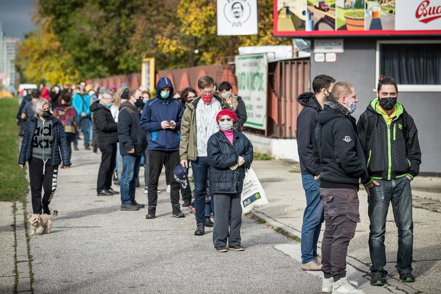 epa08788100 People wearing protective face masks wait in line at a coronavirus testing site during nationwide testing in Bratislava, Slovakia, 31 October 2020.  EPA/JAKUB GAVLAK