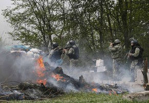 Ukrainian security force officers walk past a checkpoint set on fire and left by pro-Russian separatists near Slaviansk April 24, 2014. Ukrainian troops were digging in to a new position a few miles from the separatist-held city of Slaviansk early on Thursday, a Reuters correspondent said. Dozens of soldiers in camouflage uniform, some wearing airborne patches, were setting up sandbag defences around at least six BMD light armoured vehicles and putting up a tent near a settlement called Malynivka, some 12 km (8 miles) south of Slaviansk on the main road to the regional capital Donetsk.  REUTERS/Gleb Garanich (UKRAINE - Tags: POLITICS CIVIL UNREST MILITARY)