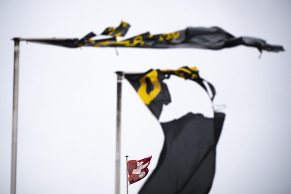 The Swiss flag and other dammaged commercial flags are waving in a storm in Echallens, Switzerland, Monday, February 10, 2020. Winter storm Ciara reached Switzerland last night. (KEYSTONE/Laurent Gillieron)