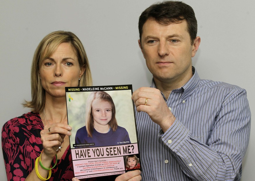 FILE - In this May 2, 2012 file photo, Kate and Gerry McCann pose for the media with a missing poster depicting an age progression computer generated image of their daughter Madeleine at nine years of age, to mark her birthday and the 5th anniversary of her disappearance during a family vacation in southern Portugal in May 2007, during a news conference in London. Madeleine McCann