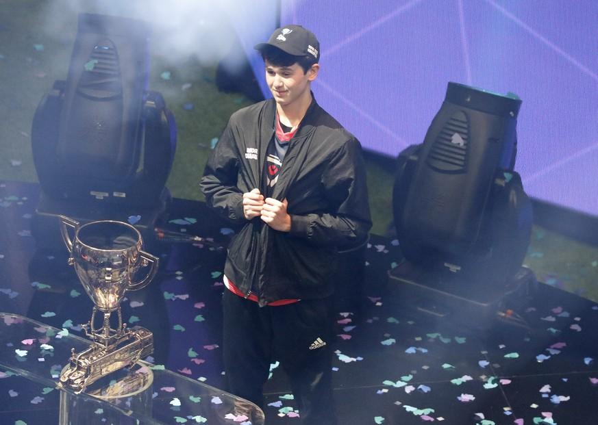 epa07746778 Fortnite player Bugha celebrates with the FortNite Championship Trophy after winning the finals of the Solo competition at the 2019 Fortnite World Cup at Flushing Meadows Arthur Ashe stadium in Queens, New York, USA, 28 July 2019.  EPA/JASON SZENES