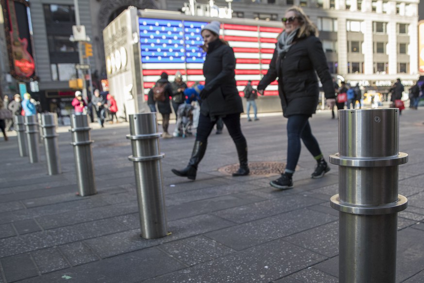 Pedestrians walk past protective barriers installed in New York's Times Square, Tuesday, Jan. 2, 2018. Hundreds of new protective barriers will be permanently installed in Times Square and other locations around New York in an effort to block vehicles from hitting pedestrians after deadly attacks last year on crowds. (AP Photo/Mary Altaffer)