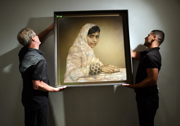 """Workers hang a painting by Jonathan Yeo titled """"Girl Reading (Malala Yousafzai)"""" before the start of the auction May 14, 2014 at Christie's Afternoon Session of Post-War and Contemporary Art in New York. The portrait is of Malala Yousafzai, the Pakistani schoolgirl shot by the Taliban for campaigning for girls' education. The sale of the painting  benefits the Malala Fund, a charity set up by Malala to support the fight for girls' right to have an education.  """"MANDATORY MENTION OF THE ARTIST UPON PUBLICATION""""   TOPSHOTS/AFP PHOTO / Timothy  A. CLARY"""