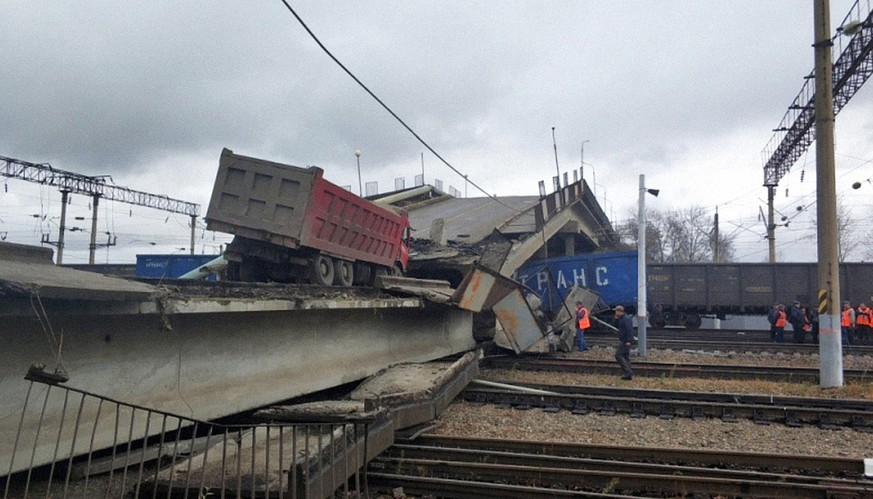 In this photo provided by Amur's region Russian Emergency Situations Ministry, a truck is seen on a road bridge that collapsed on the Trans-Siberian Railway line, in Svobodny, Far Eastern Amur Region, about 5500 km (3417 miles) East from Moscow, Russia, Tuesday, Oct. 9, 2018. According to the Emergency Ministry the driver suffered a broken leg and chest wounds. (Amur's region Russian Ministry for Emergency Situations photo via AP)