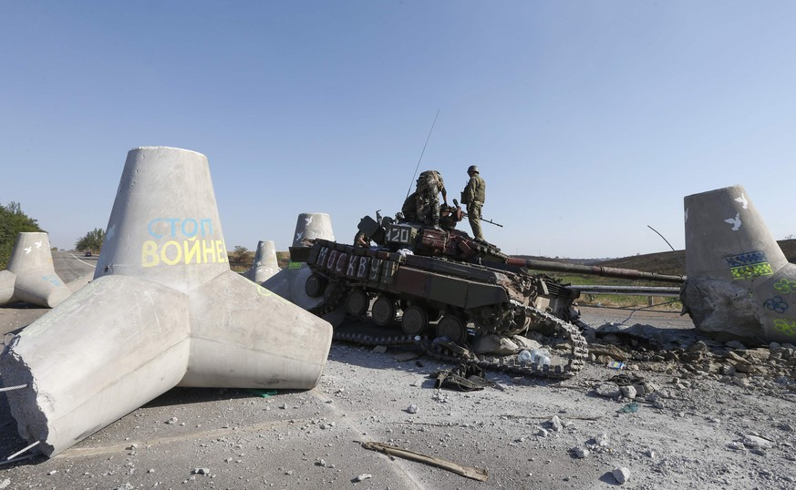 UkraInian soldiers inspect damaged tank on the outskirts of the southern coastal town of Mariupol, September 6, 2014. Russian President Vladimir Putin and Ukraine's President Petro Poroshenko agreed on Saturday in a telephone call that a ceasefire in eastern Ukraine was generally holding but said further steps were needed to make it more durable.   REUTERS/Vasily Fedosenko  (UKRAINE - Tags: CIVIL UNREST CONFLICT MILITARY)