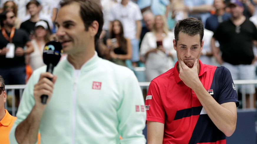 John Isner, right, listens as Roger Federer, of Switzerland, speaks following the singles final of the Miami Open tennis tournament, Sunday, March 31, 2019, in Miami Gardens, Fla. Federer won. (AP Photo/Lynne Sladky)