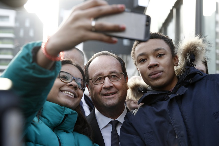 epa05799322 French President Francois Hollande (C) poses for selfies with locals during a visit to the Zac du Plateau neighborhood in the Ivry Sur Seine, south of Paris, France, 17 February 2017. The Zac du plateau is undergoing a major urban renewal due to be completed in 2018.  EPA/YOAN VALAT / POOL MAXPPP OUT