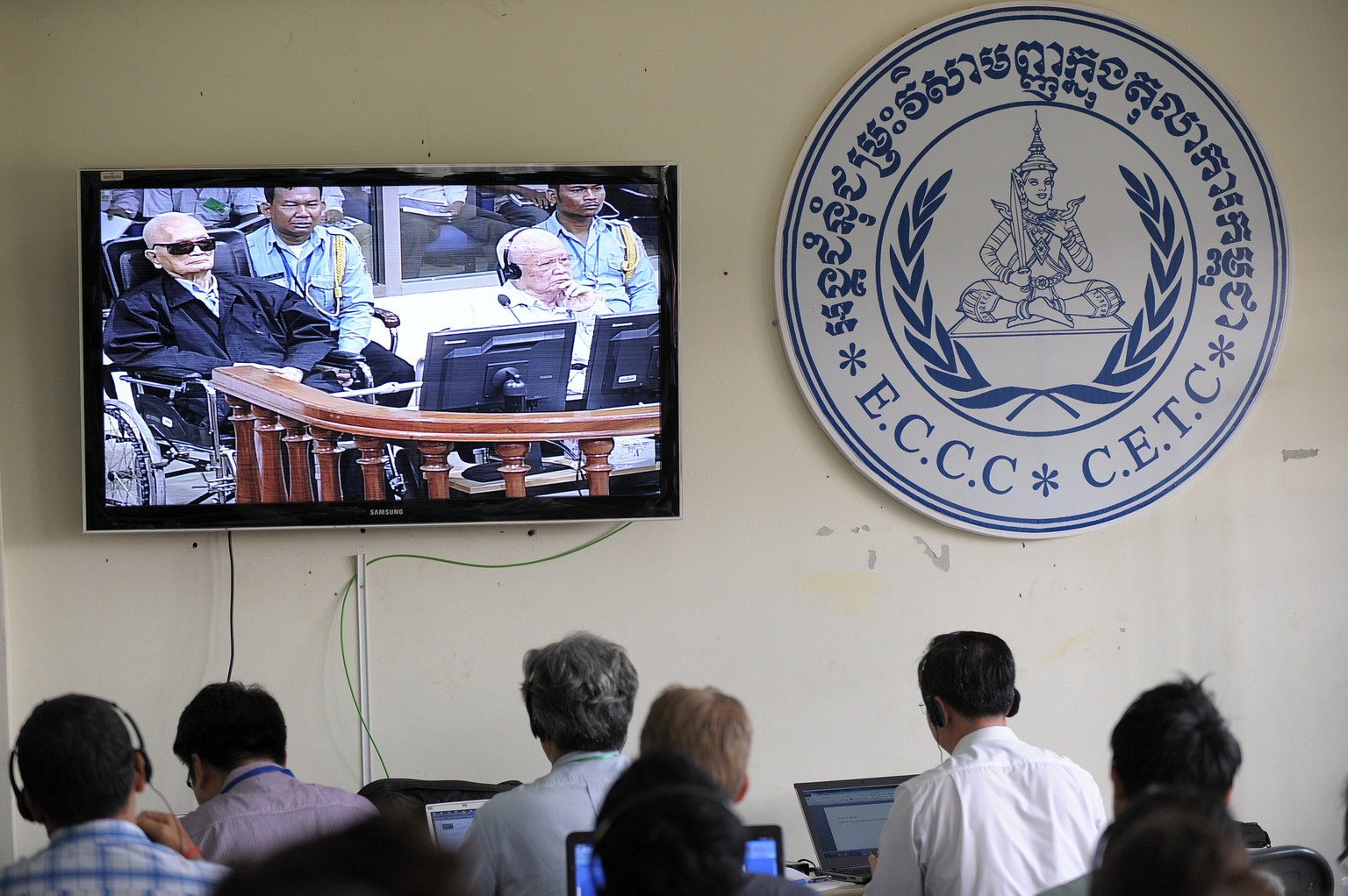 "Cambodian and international journalists watch a live video feed showing former Khmer Rouge leader ""Brother Number Two"" Nuon Chea (L) and former Khmer Rouge head of state Khieu Samphan (R) in the courtroom during their trial at the Extraordinary Chamber in the Courts of Cambodia (ECCC) in Phnom Penh on August 7, 2014.  The two former Khmer Rouge leaders face a verdict at the UN-backed tribunal in Cambodia on August 7 over allegations of crimes against humanity, marking the first time rulers of the murderous regime will be judged in a court.     AFP PHOTO / TANG CHHIN SOTHY"