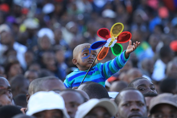 A child is seen during a car draw competition in  Harare, Saturday, June, 7, 2014. Thousands of people across Zimbabwe thronged the Borrowdale race course for a chance to win one of the 43 cars that were up for grabs at the venue. (AP Photo/Tsvangirayi Mukwazhi)