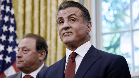 epa06760918 Actor Sylvester Stallone looks on as US President Donald J. Trump signs an Executive Grant of Clemency  for former heavyweight champion Jack Johnson in the Oval Office of the White House  in Washington, DC, USA, 24 May 2018. Former heavyweight champion Jack Johnson was convicted in 1913 under the Mann Act for taking his white girlfriend across state lines for 'immoral' purposes.  EPA/Olivier Douliery / POOL