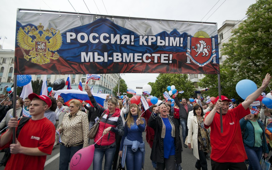People march during May Day march with poster reading: