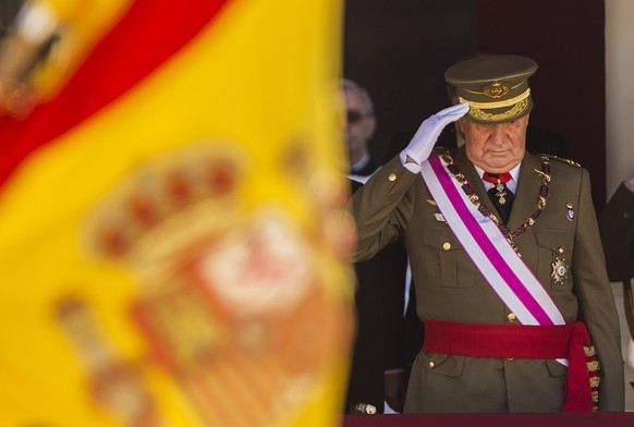 FILE - In this June 3, 2014 file photo then King Juan Carlos attends a military ceremony in San Lorenzo de El Escorial, outside Madrid, Spain. The royal family's website on Monday Aug. 3, 2020, published a letter from Spain's former monarch, King Juan Carlos I, saying he is leaving Spain to live in another country, amidst a financial scandal. (AP Photo/Daniel Ochoa de Olza, File) Spain King Juan Carlos,Crown Prince Felipe