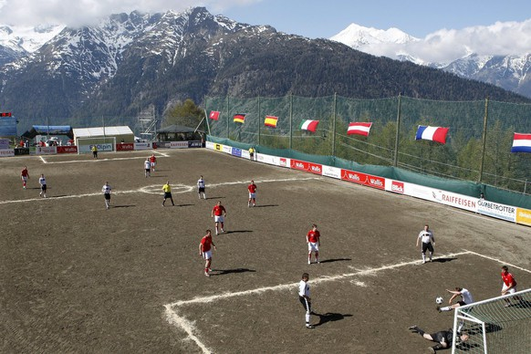 Amateur football from Switzerland wearing the red dresses play during a match against amateur football players from Germany in the white dresses, at the European Mountain Village Soccer Championship, in Gspon, Switzerland, Friday, May 23, 2008. The mountain villages of Staldenried and Gspon organised a soccer tournament on 2008 meters above sea level on the highest football pitch of Europe, with eight teams from eight nations during three days. (KEYSTONE/Jean-Christophe Bott)