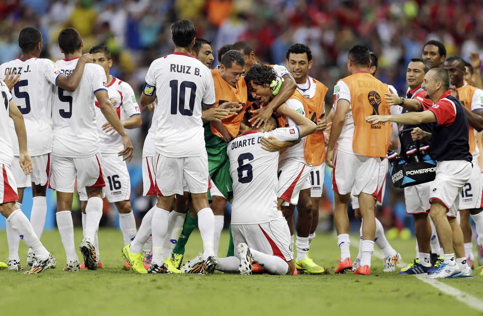 Costa Rican players swarm over Costa Rica's Oscar Duarte (6) after he scored his side's second goal during the group D World Cup soccer match between Uruguay and Costa Rica at the Arena Castelao in Fortaleza, Brazil, Saturday, June 14, 2014.  (AP Photo/Natacha Pisarenko)