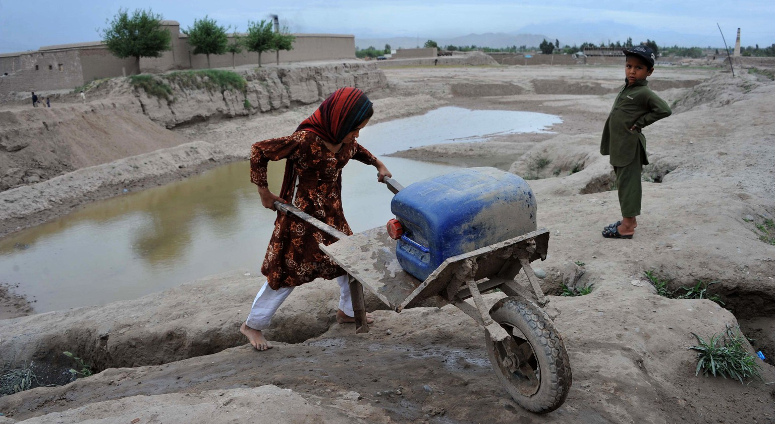 An Afghan child uses a wheelbarrow to transport a water container through the temporary settelment where she lives on the outskirts of Jalalabad on May 8, 2014. Afghanistan's economy is recovering from decades of conflict but despite the significant improvement in the last decade it is extremely poor, and highly dependent on foreign aid.  AFP PHOTO / Noorullah SHIRZADA