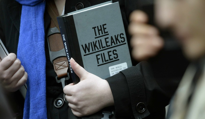 A supporter of WikiLeaks founder julian Assange holds a copy of The WikiLeaks Files outside the Ecuadorian embassy in central London, Britain February 5, 2016. Assange should be allowed to go free from the Ecuadorian embassy in London and be awarded compensation for what amounts to a three-and-a-half-year arbitrary detention, a U.N. panel ruled on Friday.   REUTERS/Toby Melville