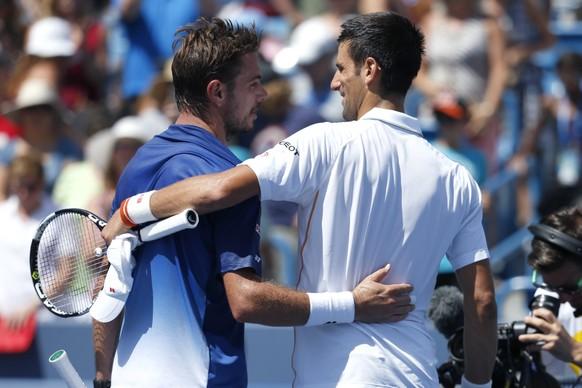 Novak Djokovic, of Serbia, right, hugs Stanislas Wawrinka, of Switzerland, after their quarterfinal match at the Western & Southern Open tennis tournament, Friday, Aug. 21, 2015, in Mason, Ohio. Djokovic defeated Wawrinka 6-4, 6-1. (AP Photo/John Minchillo)