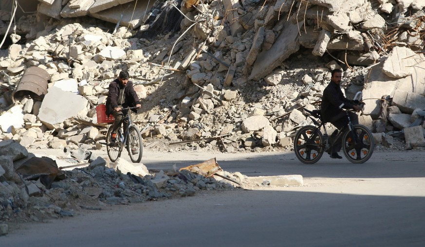 Men ride bicycles near rubble of damaged buildings in a rebel-held besieged area in Aleppo, Syria November 6, 2016. REUTERS/Abdalrhman Ismail