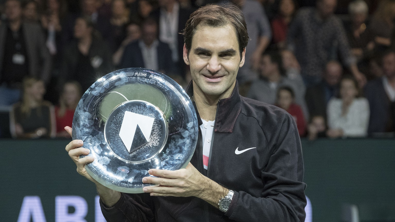 Roger Federer of Switzerland holds the trophy as he celebrates winning his match against Bulgaria's Grigor Dimitrov in two sets, 6-2, 6-2, in the men's singles final of the ABN AMRO world tennis tournament at the Ahoy stadium in Rotterdam, Netherlands, Sunday, Feb. 18, 2018. (AP Photo/Patrick Post)