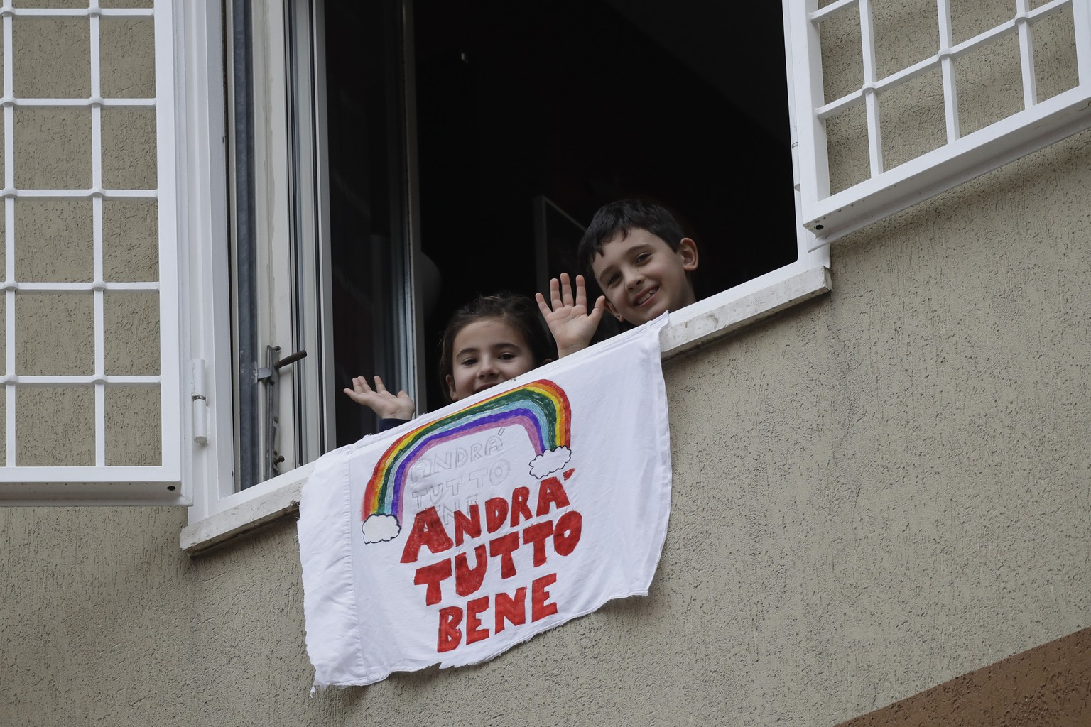In this photo taken on Friday, March 13, 2020, Francesco and Greta Innominati wave after placing a banner reading