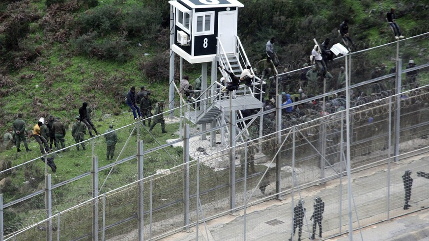 epa05694908 (FILE) - A file photograph showing Moroccan Police looking at immigrants trying to jump the six-meter-high fence in Ceuta, Spanish enclave on the north of Africa, 09 December 2016. Media reports on 02 January 2017 state that more than 1,100 African migrants attempted to storm a border fence in Ceuta injuring fifty Moroccans and five Spanish border guards. Only two migants made it across the border but both needed hospital treatment following their breach.  EPA/REDUAN