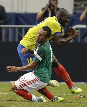 In this May 31, 2014, photo, Mexico's Luis Montes collides with Ecuador's Segundo Castillo, rear, as the two were competing for the ball during the first half of a friendly soccer match, in Arlington, Texas. Montes, who took the brunt of the collision was stretchered off the pitch after fracturing his right tibia and fibula. (AP Photo/Tony Gutierrez)