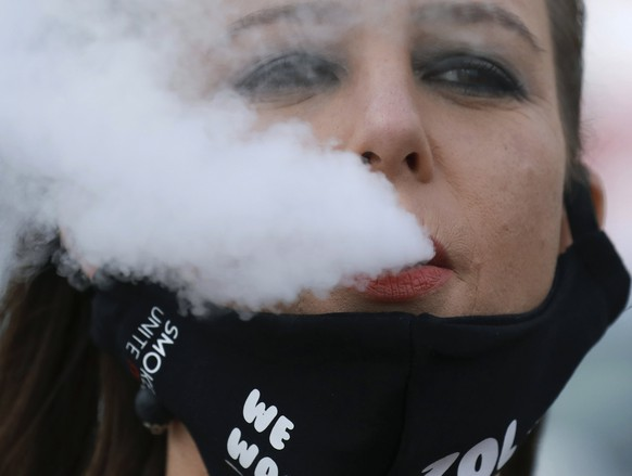 In this June 2, 2020 photo, a demonstrator exhales smoke during a protest against the tobacco ban outside parliament in Cape Town, South Africa. An effort to lift South Africa