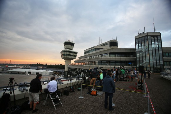 epa04316362 Photographers and TV crews gather on a roof of the Tegel airport in Berlin as they wait for the arrival of the plane carrying home the team of Brazil 2014 FIFA Soccer World Cup winner Germany, in Berlin, early 15 July 2014. Due to a technical delay the plane is expected to arrive at the German capital some two hours later. The German team on 13 July 2014 had won the Brazil 2014 FIFA Soccer World Cup final against Argentina by 1-0 to win the title for the fourth time after 1954, 1974 and 1990.  EPA/JENS BUETTNER