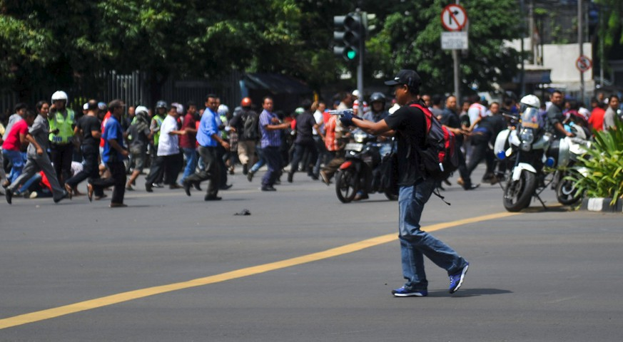 A man is seen holding a gun towards the crowd in central Jakarta, Indonesia, in this picture provided to Reuters by Xinhua News Agency January 14, 2016. REUTERS/Veri Sanovri/Xinhua ATTENTION EDITORS - THIS IMAGE WAS PROVIDED BY A THIRD PARTY. REUTERS IS UNABLE TO INDEPENDENTLY VERIFY THE AUTHENTICITY, CONTENT, LOCATION OR DATE OF THIS IMAGE. IT IS DISTRIBUTED EXACTLY AS RECEIVED BY REUTERS, AS A SERVICE TO CLIENTS. FOR EDITORIAL USE ONLY. NOT FOR SALE FOR MARKETING OR ADVERTISING CAMPAIGNS. NO RESALES. NO ARCHIVE. CHINA OUT. NO COMMERCIAL OR EDITORIAL SALES IN CHINA       TPX IMAGES OF THE DAY