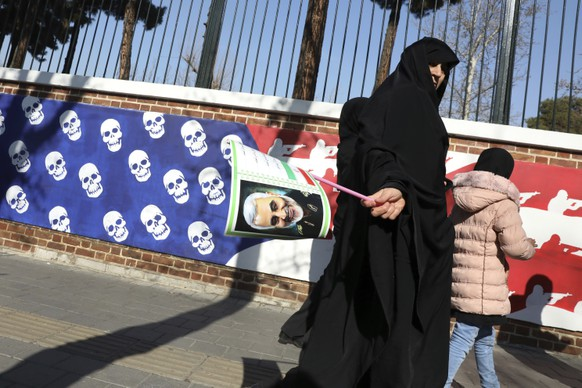 A mourner holds a poster of Iranian Gen. Qassem Soleimani, as she walks back from a funeral ceremony for him and his comrades, who were killed in Iraq in a U.S. drone attack on Friday, passing a satirical drawing of the U.S. flag painted on the wall of the former U.S. Embassy in Tehran, Iran, Monday, Jan. 6, 2020. Funeral ceremonies for Soleimani drew a crowd said by police to be in the millions, on Monday in Tehran, where his replacement vowed to take revenge. (AP Photo/Vahid Salemi)