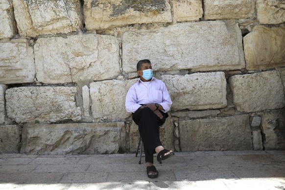 A Muslim man wears a protective face mask as he sits outside the Dome of the Rock and al-Aqsa mosque compound, which remains shut to prevent the spread of coronavirus in Jerusalem's Old City, Friday, May, 29, 2020. Muslim faithful gathered for traditional Friday prayers outside one of the gates leading to the Al Aqsa compound in Jerusalem's Old City, Muslims third holiest site. The compound is to reopen Sunday. (AP Photo/Mahmoud Illean)