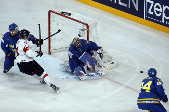 epa05972826 Henrik Lundqvist of Sweden (C) in action against Fabrice Herzog of Switzerland during the IIHF Ice Hockey World Championship 2017 quarter final game between Switzerland and Sweden in Paris, France, 18 May 2017.  EPA/ETIENNE LAURENT