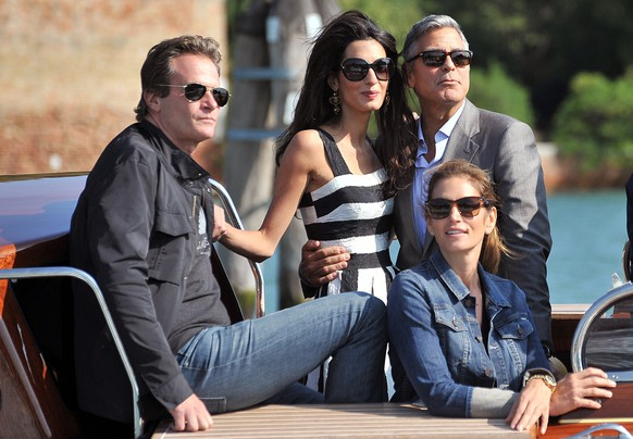 George Clooney, top right, his fiancee Amal Alamuddin, Cindy Crawford, bottom right and her husband Rande Gerber arrive in Venice, Italy, Friday, Sept. 26, 2014. George Clooney and his fiancee Amal Alamuddin arrived in Venice on Friday for their weekend wedding extravaganza, accompanied by loved ones and trailed by a clutch of photographers who recorded their passage along the picturesque Grand Canal. (AP Photo/Luigi Costantini)