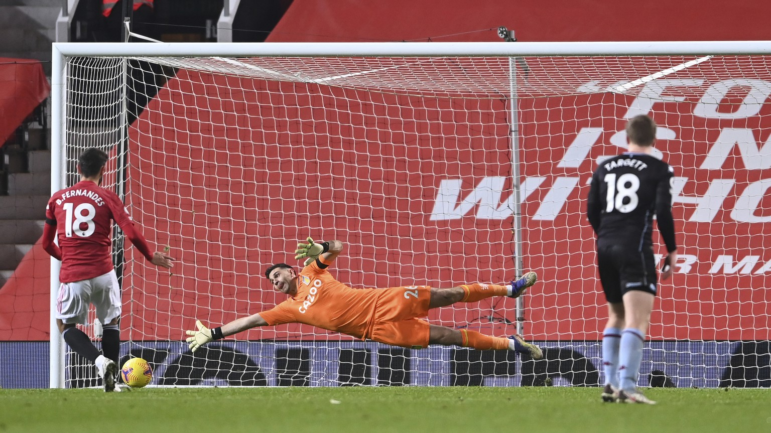 Manchester United's Bruno Fernandes, left scores from the penalty spot for his sides 2nd goal of the game past a diving Aston Villa's goalkeeper Emiliano Martinez during the English Premier League soccer match between Manchester United and Aston Villa at Old Trafford in Manchester, England, Friday, Jan. 1, 2021. (Lawrence Griffiths/ Pool via AP)