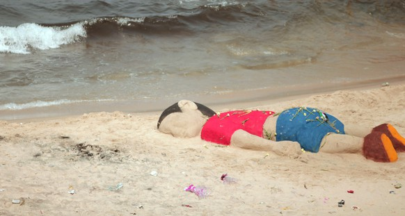 In this Monday Sept. 7, 2015 photo, a sand sculpture pays tribute to three year-old Syrian boy Aylan Kurdi, whose haunting image hammered home the Syrian migrant crisis to the world. He died along with 5-year-old brother and their mother when their small rubber boat capsized as it headed for Greece. (AP Photo)