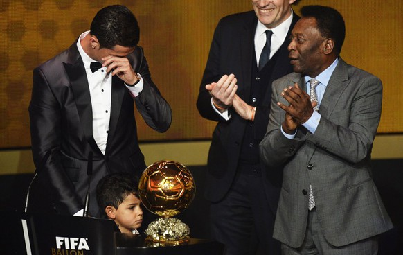 epa04019373 Real Madrid's Portuguese striker Cristiano Ronaldo (L) cries as he receives the FIFA Men's World Player of the Year 2013 award during the FIFA Ballon d'Or 2013 gala at the Kongresshaus in Zurich, Switzerland, 13 January 2014. At right Brazilian soccer legend Pele.  EPA/STEFFEN SCHMIDT