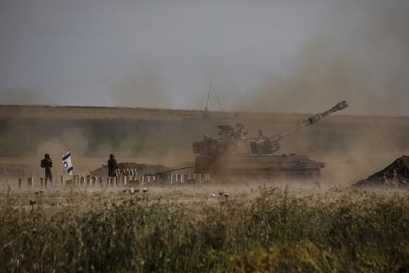 An Israeli artillery unit fires toward targets in the Gaza Strip, at the Israeli-Gaza border, Sunday, May 16, 2021. (AP Photo/Heidi Levine)