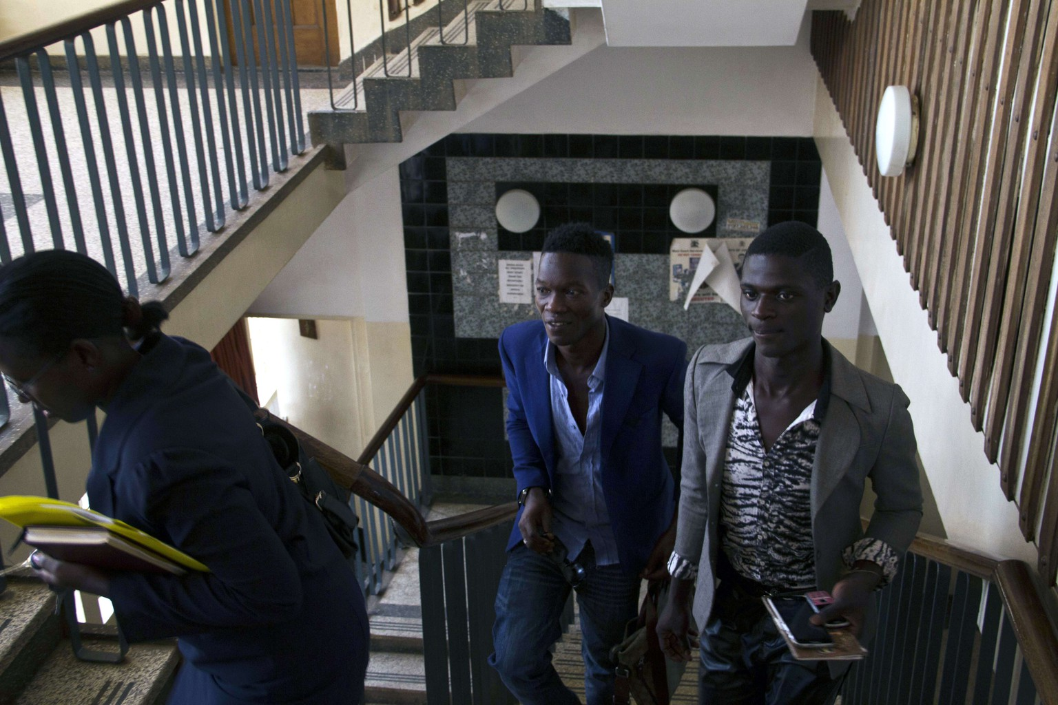 Two Ugandan men, Jackson Mukasa (R) and Kim Mukisa (L) arrive at the Buganda road Magistrate's Court on June 12, 2014 where they are charged with unnatural offences. Their case was adjourned to July 7, 2014 after lack of witnesses. The couple, if found guilty, would be the first in the East African nation to go on trial since President Yoweri Museveni signed the anti-gay bill into law in February that has seen other cases end in dismissal for want of prosecution or have remained pending. AFP PHOTO/ ISAAC KASAMANI
