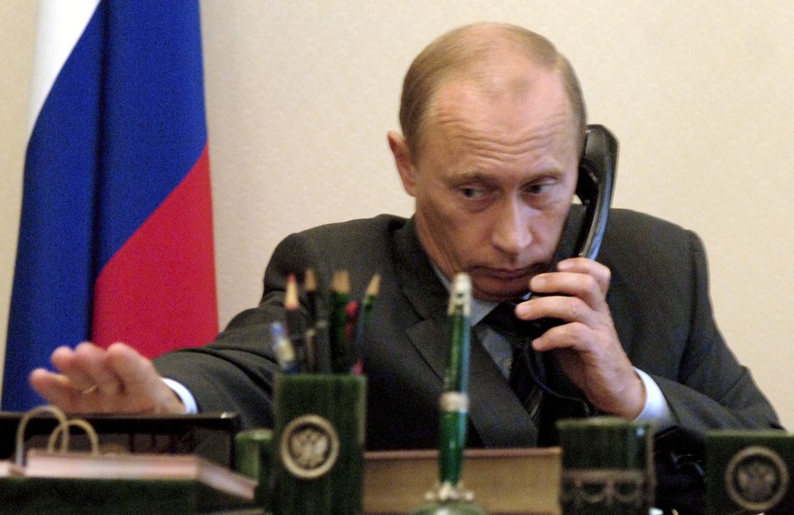 Russian President Vladimir Putin speaks by a phone at his residence Novo-Ogarevo, just outside Moscow on Friday, Aug. 5, 2005.  A Russian mini-submarine with seven sailors aboard has been  caught on a fishing net and is stuck on the sea floor off Russia's Pacific Coast, navy officials said Friday. Putin made no comment on the Russian navy accident. (AP Photo) **  MAGAZINES OUT **