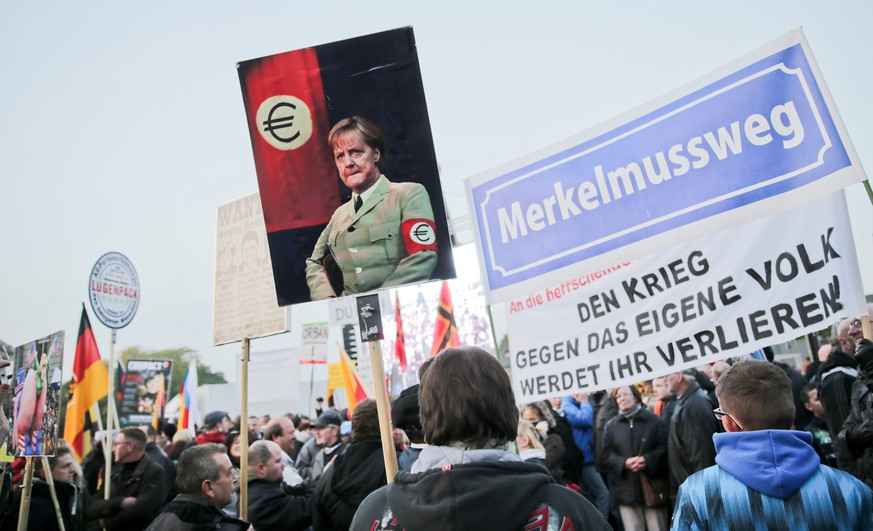 epa04984204 A demonstrator's sign shows German Chancellor Merkel in uniform wearing a Euro armband in Dresden, Germany, 19 October 2015. One year ago, Pegida (Patriotic Europeans against the Islamification of the West), demonstrated on the streets for the first time. The anti-immigrant group is planning a demonstration on its anniversary.  EPA/MICHAEL KAPPELER