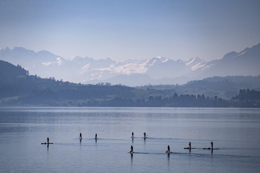 A group of stand up paddlers on the Lake of Zug on a sunny and mild Sunday, February 21 2021. In some regions of Switzerland the temperatures rose to 20 degrees. (KEYSTONE/Alexandra Wey)
